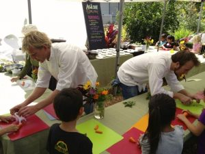 Private Maui Chef Dan Fiske and Capische? Chef de Cuisine Christopher Kulis assist Kihei Elementary School students in preparing garden-grown ingredients for a stir fry recipe