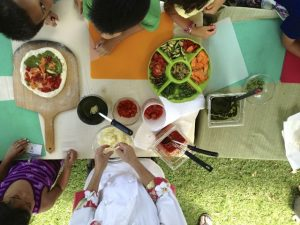 Private chef Jana McMahon assists Kihei Elementary School students in creating school garden veggie pizzas