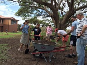 Visiting Volunteers help move some soil.